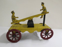 Pull toy, c. 1914. The seesaw moves up and down as the wheels turn.