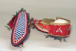 "Burial Moccasins, 1875-1925, Niitsitapii (Blackfoot) or Sioux. These are referred to as ""burial moccasins"" because of the beading on the soles signifying ceremonial use. They have quill work on the upper part, as well as feather and metal details. These moccasins are an example of how traditional natural materials and newer trade materials were used together."