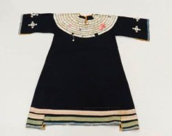 This dress, made around 1880-1920 by a Plains group, is decorated with silk ribbon along the bottom and dentalium shells on the chest area and in cross shapes on the sleeves.