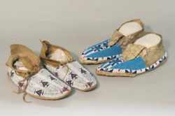 Moccasins, 1880-1920, possibly Inunaina (Arapaho), and Sioux. The white moccasins are women's or children's based on their size, while the blue moccasins are men's.